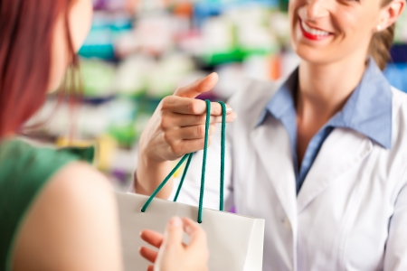 farmacia: Farmac�utico femenina con un cliente femenino en su farmacia