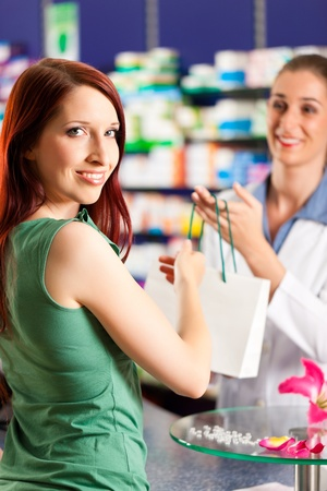 competent: Female pharmacist with a female customer in her pharmacy