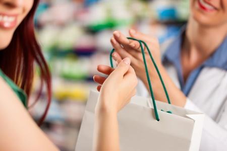 Female pharmacist with a female customer in her pharmacy photo