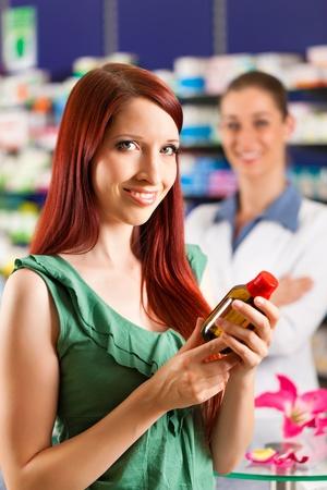 Female customer in a pharmacy - in the background the pharmacist Stok Fotoğraf