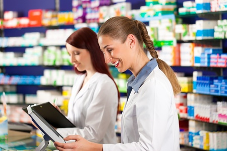drugstore: Farmacéutico con el asistente de la mujer en pie de farmacia en el cajero automático