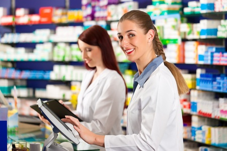 Pharmacist with female assistant in pharmacy standing at the cashpoint Stock Photo - 10718100