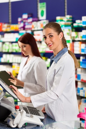 Pharmacist with female assistant in pharmacy standing at the cashpoint photo