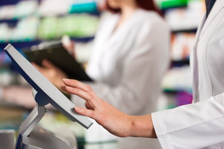 checkout: Pharmacist with female assistant in pharmacy standing at the cash point Stock Photo