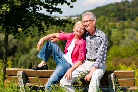 Visibly happy mature or senior couple outdoors arm in arm deeply in love, both are sitting on a bench  photo
