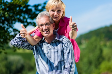 Visibly happy mature or senior couple outdoors arm in arm, he is carrying her piggyback photo