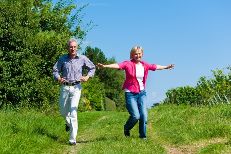 Visibly happy mature or senior couple outdoors having a walk in a playful way  photo