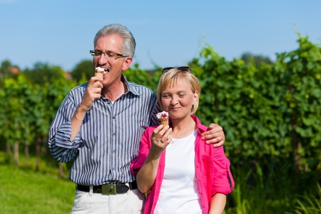 Visibly happy mature or senior couple outdoors having a walk and eating ice cream photo