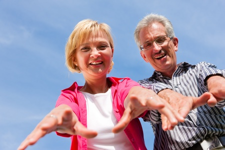 Visibly happy mature or senior couple outdoors arm in arm having a walk  photo