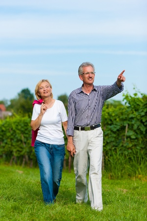 Visibly happy mature or senior couple outdoors hand in hand having a walk    photo