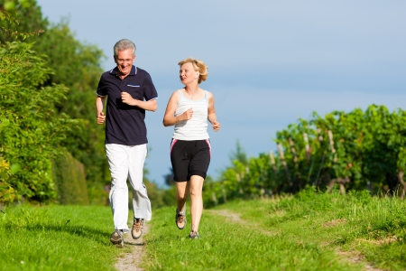 sunlit: Mature or senior couple doing sport outdoors, jogging down a path in summer