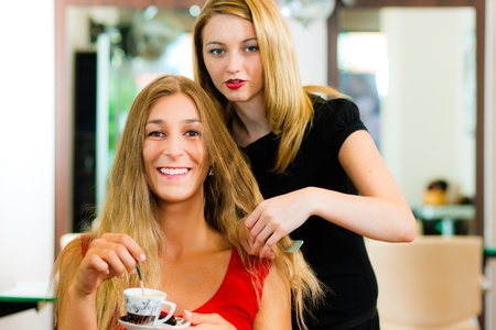 advise: Woman at the hairdresser getting advise on her hair styling, the girls are drinking Cappuccino