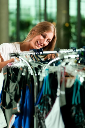 Woman browsing through clothes on a rack in a fashion store Stock Photo - 10770008