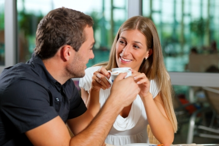 Young couple - man and woman - drinking coffee in a cafe in front of a glass  photo