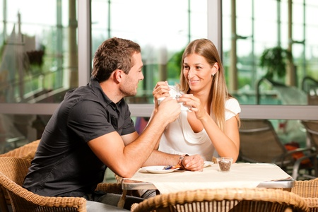 drinking coffee: Young couple - man and woman - drinking coffee in a cafe in front of a glass
