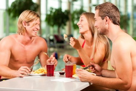 pool bar: Three young people - woman and two men - eating and drinking in a restaurant at a public swimming pool