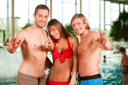 standing water: Three young people - woman and two men - at a public swimming pool standing in front of the water Stock Photo
