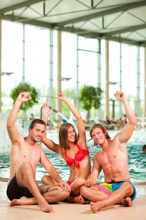pool fun: Three young people - woman and two men - at a public swimming pool, sitting on the floor having fun Stock Photo