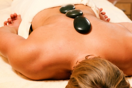man in wellness and spa setting having a hot stone therapy session photo