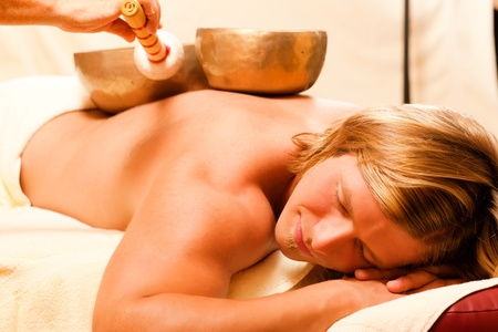 Man in wellness and spa setting having a singing bowl therapy session   Stock Photo - 10770035