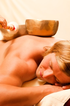 Man in wellness and spa setting having a singing bowl therapy session   photo