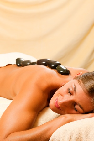 Woman in wellness and spa setting having a hot stone therapy session photo