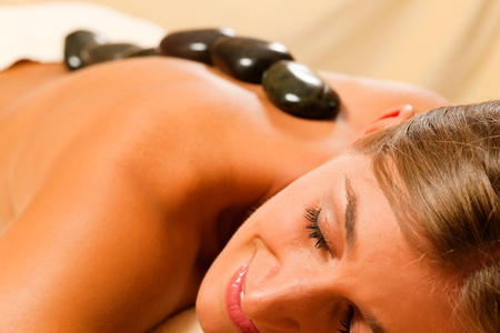 Woman in wellness and spa setting having a hot stone therapy session Stock Photo - 10769998