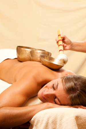 Woman in wellness and spa setting having a singing bowl therapy session   photo
