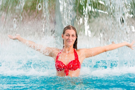 woman a public swimming pool standing under a water gadget photo
