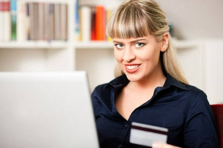 emphasized: Woman sitting with a laptop in her home living room in front of a book shelf shopping or doing banking transactions online in the Internet, emphasized by her holding a credit card
