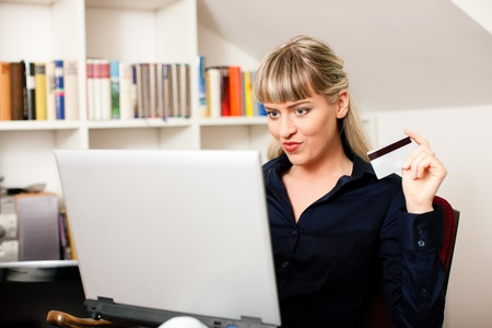 Woman sitting with a laptop in her home living room in front of a book shelf shopping or doing banking transactions online in the Internet, emphasized by her holding a credit card Stock Photo - 10899531