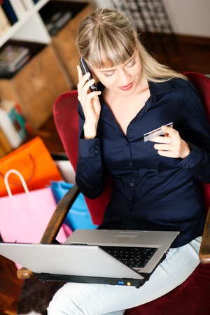 emphasized: Woman sitting with a laptop in her home living room in front of a book shelf shopping or doing banking transactions online in the Internet, emphasized by shopping bags in the background and her holding a credit card