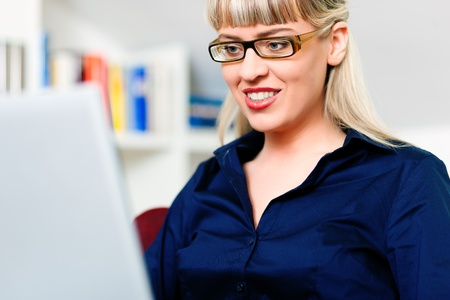 Woman sitting in front of a bookshelf, working with a laptop in the internet from home, she is a telecommuter Stock Photo - 10899493