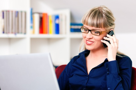 telecommuter: Woman sitting in front of a bookshelf using her telephone, working with a laptop in the internet from home, she is a telecommuter  Stock Photo
