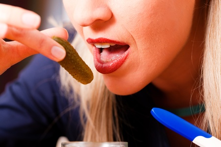 hormonal: Pregnant woman - she hold a pregnancy test in her hand - is hungry for sour pickles due to change in her hormonal balance  Stock Photo
