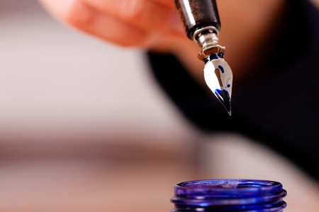 person (only hand to be seen) writing a letter on paper with a pen and ink, in the foreground there is an ink pot  photo