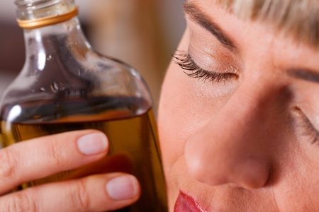 Woman sitting at home drinking way too much brandy, she is addicted   photo