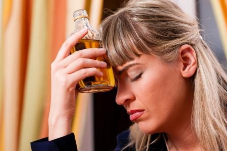 borracho: Mujer sentada en camino a casa, bebiendo aguardiente demasiado, ella es adicta Foto de archivo