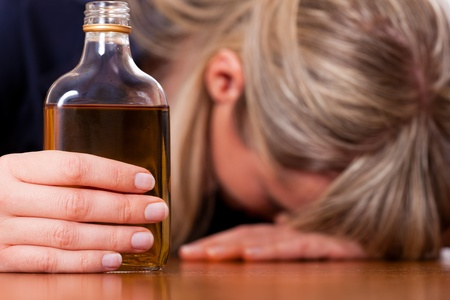 comforting: Woman sitting at home drinking way too much brandy, she is addicted
