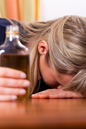 Woman sitting at home drinking way too much brandy, she is addicted Stock Photo - 10899507