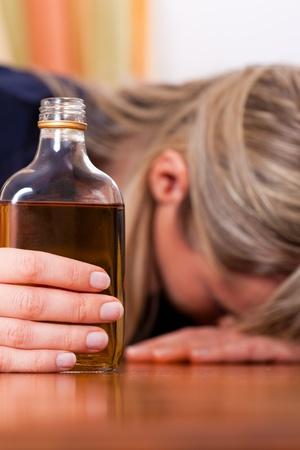alcoolisme: Femme assise � la maison fa�on potable brandy trop, elle est accro