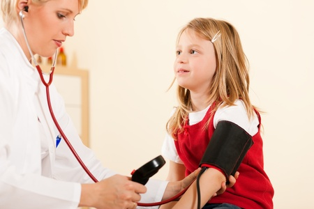 Female doctor measuring blood pressure of a child patient using the pressure sleeve and her stethoscope  photo