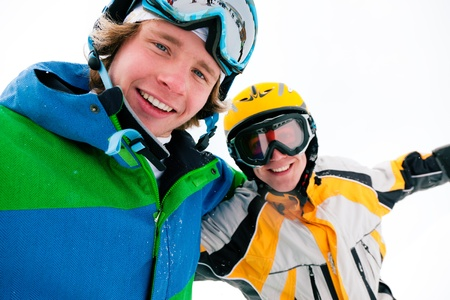 Skier and snowboarder in the snow posing for the camera   photo