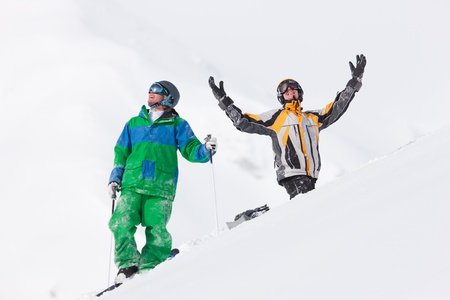 Skier and snowboarder in the snow giving five an alpine winter landscape in anticipation of the next downhill race   photo