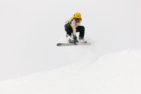 Snowboarder in the alps jumping over an edge of snow grabbing his snowboard photo