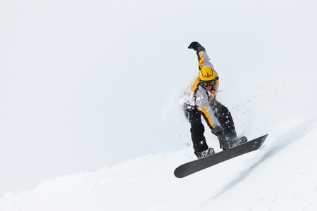 snowboarder jumping: Snowboarder in the alps jumping over an edge of snow grabbing his snowboard