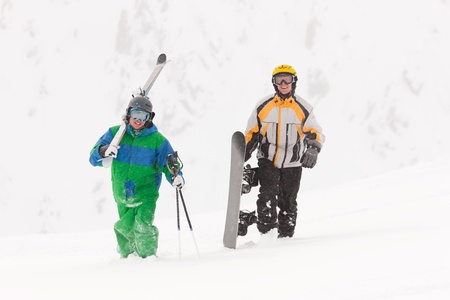 ski walking: Skier and snowboarder carrying their gear on an alpine winter day