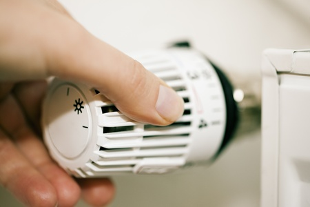 Female hand turning down the thermostat - symbol for saving of energy consumption  photo