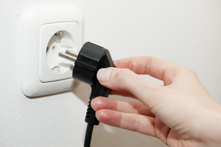 enchufe: Mano femenina desconectar un enchufe de una toma de corriente, metáfora de ahorro de energía eléctrica
