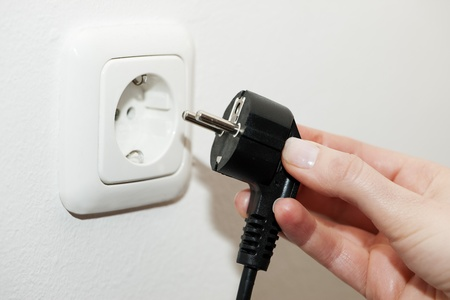 Female hand unplugging a plug from a socket, metaphor for saving electrical energy  photo
